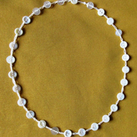 A button necklace comprising small pearly and white buttons on a crocheted chain