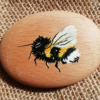 Hand painted wooden pebble.