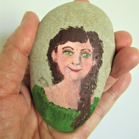 Girl with brown hair painting. Rock painting. Stone art.