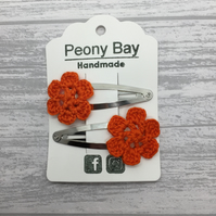 Girl's hair clips with orange crocheted flowers