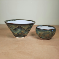 A pair of hand thrown pale blue and multi stoneware bowls