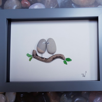 Two besotted grey pebbles on a leafy driftwood branch