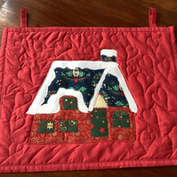 Appliqué xmas cottage wall hanging.