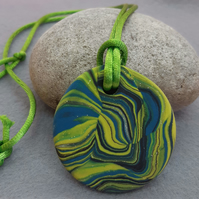 Brightly coloured round polymer clay pendant