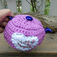 crochet tea cosy with hand embroidered blossom on a felt heart