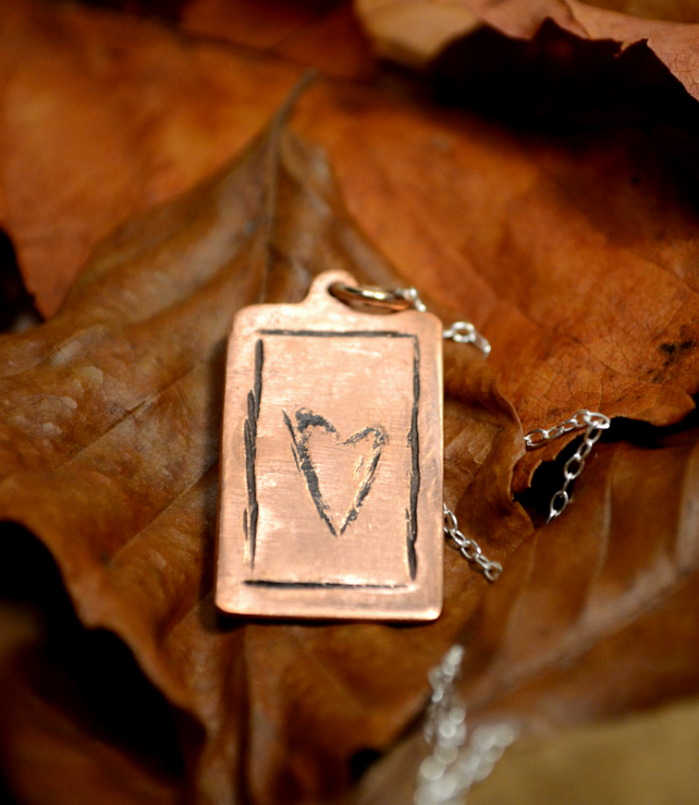 Dog tag style copper heart pendant on sterling silver chain.