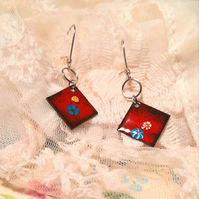 Red enamel drop earrings, with yellow and blue floral design.