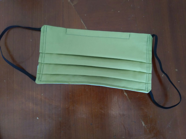 Green reusable cotton face mask with filter pocket and aluminium nose bridge.