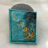 Handmade felted brooch with orange stitch