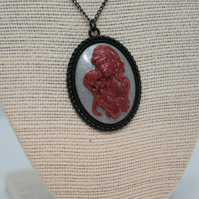 Zombie lady holding a skull pendant