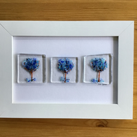 Picture. Blue trees fused glass picture in 6x4 white frame.