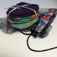 Eight face scrubbies in shades of purple and green and coordinating net washbag.
