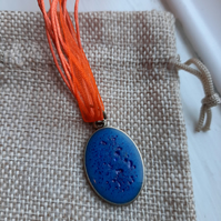Deep Blue Circle resin pendent with a orange organza ribbon necklace