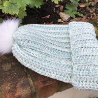 Winter hat in turquoise and cream blend acrylic yarn with faux fur Pom pom