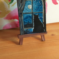 Mini canvas of a cat looking out of a window at night