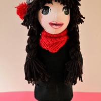Doll in a hat with red pompoms