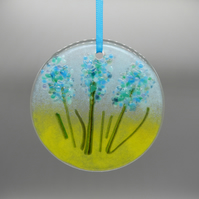 A fused glass bunch of blue flowers - very pretty in a window