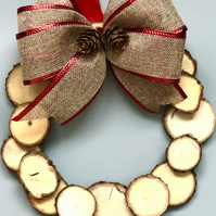 Wooden wreath with natural slices of wood and a large burlap bow