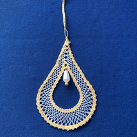 Bobbin lace pendant in white, with a golden yellow border.