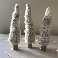 Three white hand knitted trees on wooden trunks