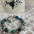 Blue beaded bracelet with silvery spacers and charms