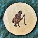 Lady Golfer 10cm diameter wooden drink coaster or fridge magnet, wood-burned.