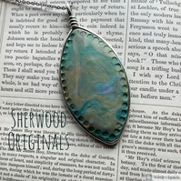 Unique design pendant necklace in hues of green and blue.