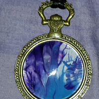 Handmade steampunk pocket watch style pendant, blue and purple.