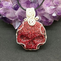 Red skull pendant wire wrapped with silver plated wire with black cord chain.