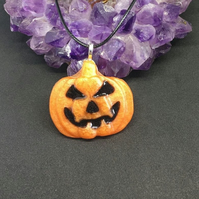 Pumpkin pendant on black cord chain.