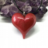 Ruby red metallic puffy heart statement pendant with black cord necklace.