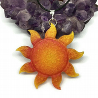Glitter Sun large statement pendant with a black cord chain.