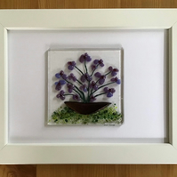 Picture of purple flowers in fused glass in 5x7ins white frame.