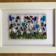 Picture of blue, pink, lilac flowers in fused glass in 5x7ins white frame.