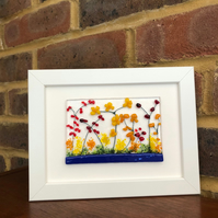 Picture of yellow, red, orange flowers in fused glass in 5x7ins white frame.