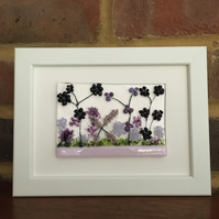 Picture of purple and lilac flowers in fused glass in 5x7ins white frame.