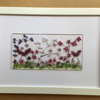 Pink and purple flowers fused glass picture in white A4 frame.
