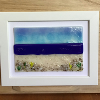 Blue sea and beach fused glass picture in 5x7ins white frame.