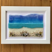 Turquoise sea and beach fused glass picture in 5x7ins white frame.
