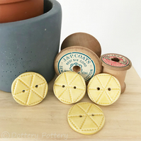 Set of four bright yellow ceramic handmade buttons