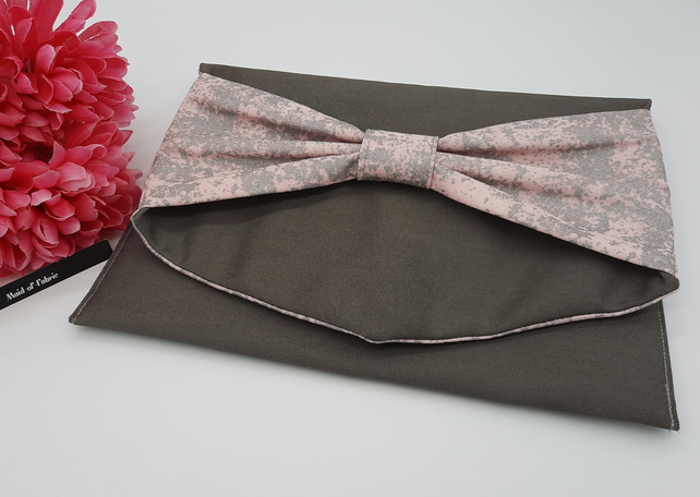 Bow clutch bag in grey denim with pink silver glitter lining.