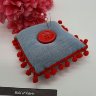 Pin cushion in denim with red bobble trim.