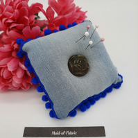 Pin cushion in upcycled denim with blue bobble trim and a rose button.