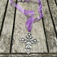 Metal detailed cross on purple ribbon necklace