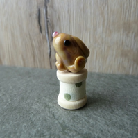 glass hare on wooden spool