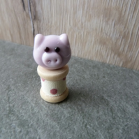 glass pig on a wooden bobbin