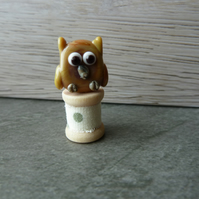 glass owl on wooden spool