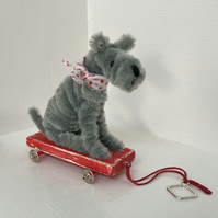 Miniature Terrier on Pull Along Trolley with Wheels.
