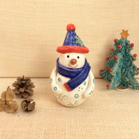 Ceramic snowman figurine with bobble hat, snowflakes, blue and red scarf