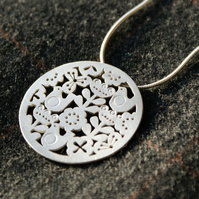 Silver flower and bird statement pendant
